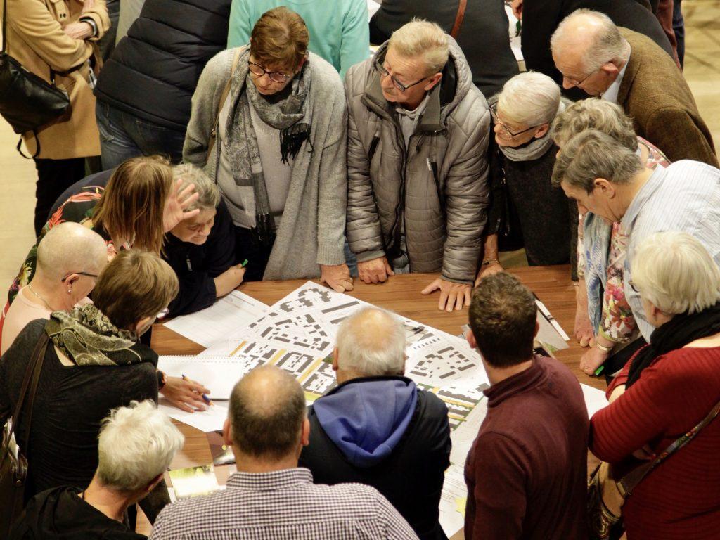 Bewoners en begeleider rondom een tafel nemen samen het ontwerp door